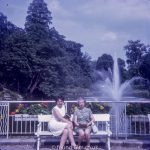 Two ladies posing by a lake and fountain