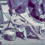 Woman sunbathing in a deckchair on a beach