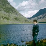 Man standing by a lake and mountain