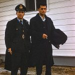 Two servicemen by a wooden building – April 1961