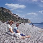 Women sitting on a pebble beach