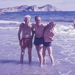Three men in the sea on a beach