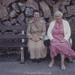 A portrait of two ladies on a bench