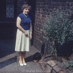Woman with a dog standing next to a brick wall