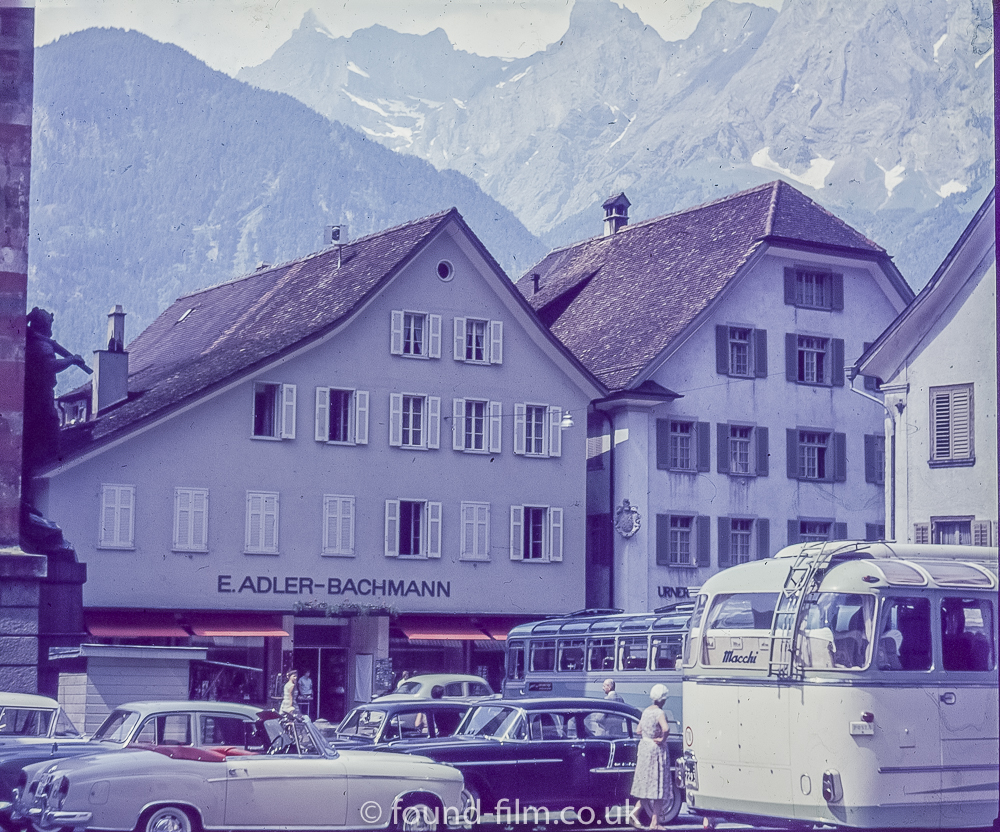 A Swiss Street Scene showing cars and a coach believed to be about 1960