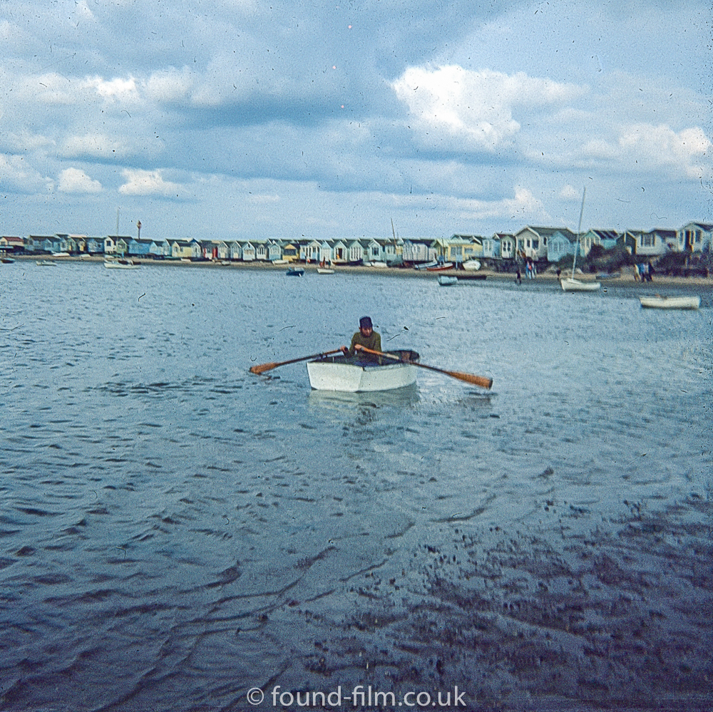 A man rowing a dingy close to the beach