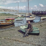 A Man sitting on a green boat by the sea